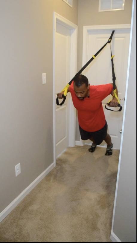 MicVinny using a TRX on a door in a hall way