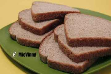 Six slices of wheat bread with Micvinny logo on a green plate. Is eating bread bad?