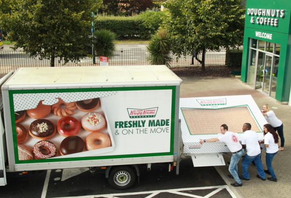 four people load a huge box of donuts into a truck.