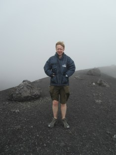 John, shrouded in cloud, standing on the sandy volcanic soil.
