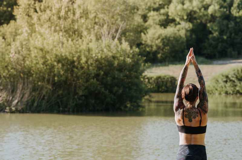 anonymous tattooed woman practicing yoga against river in summer