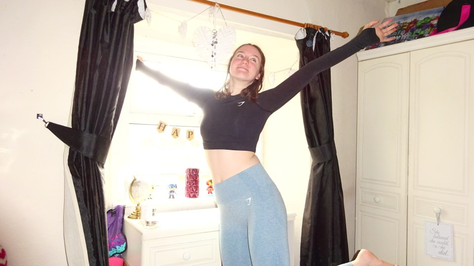 Me in Gymshark clothing in a pose with my foot in the air and arms up smiling to show my enjoyment fuelling my intrinsic motivation