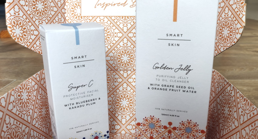 Smart Skin moisturiser and cleanser boxes with decorative background.