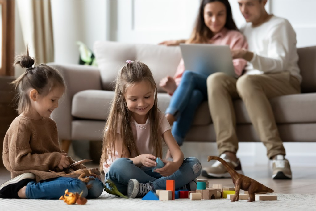 Happy little kid siblings having fun playing toys on floor while parents sit on sofa using laptop