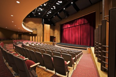 photo of auditorium curved stage, wood paneled proscenium red curtains, curved rows of seating