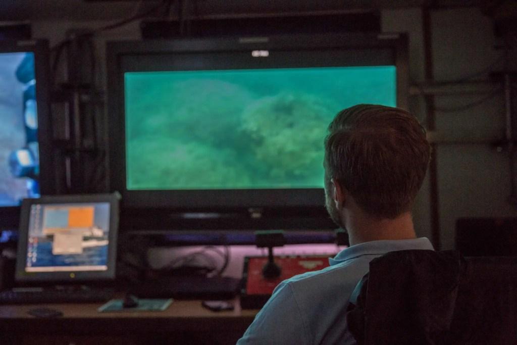 Mateusz Polakowski looking at a screen showing underwater camera footage