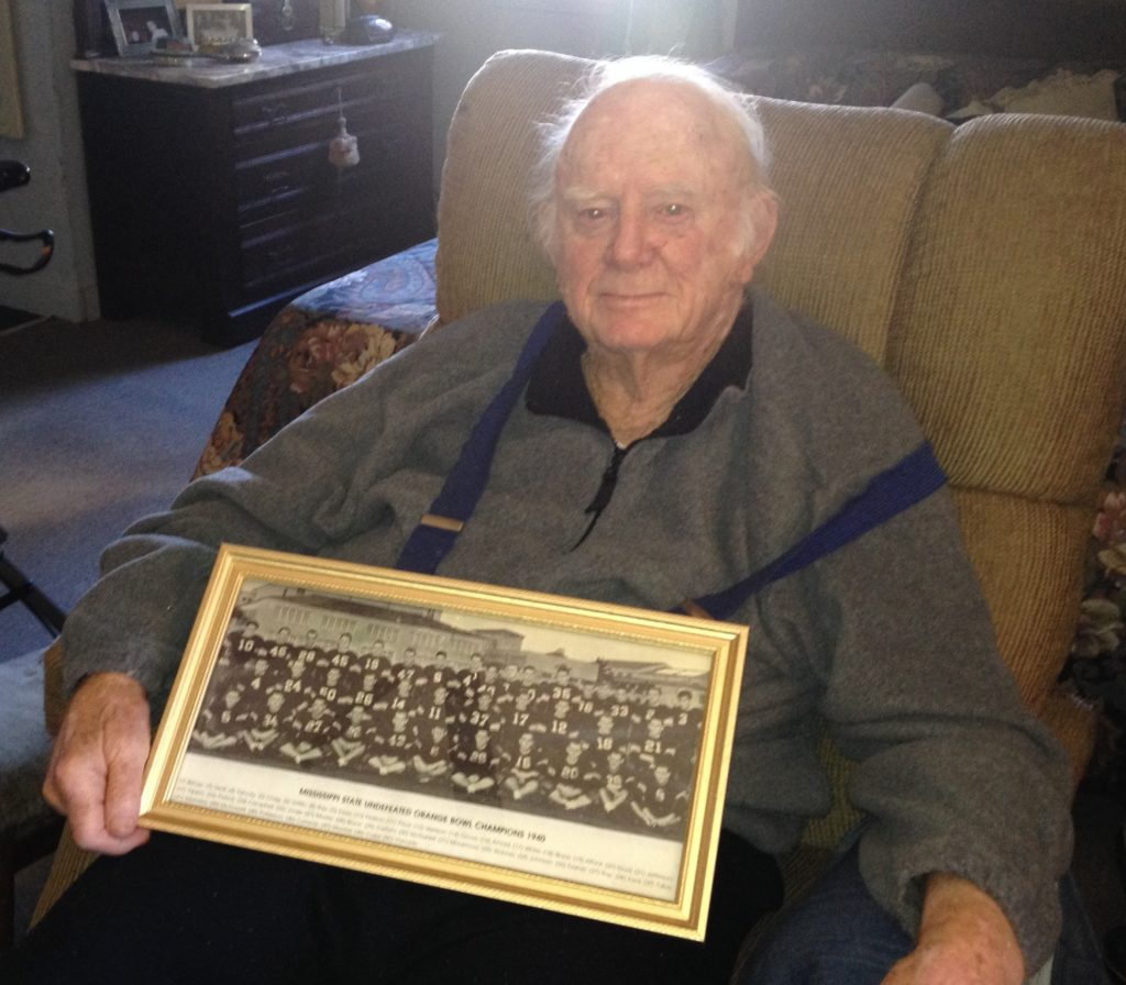 Tut Patterson, 93, holds his prized photo of Mississippi State's 1941 Orange Bowl team.