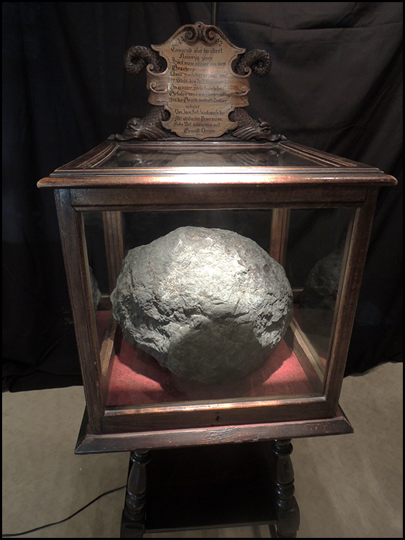 The famous and historic Ensisheim meteorite inits wooden display case.