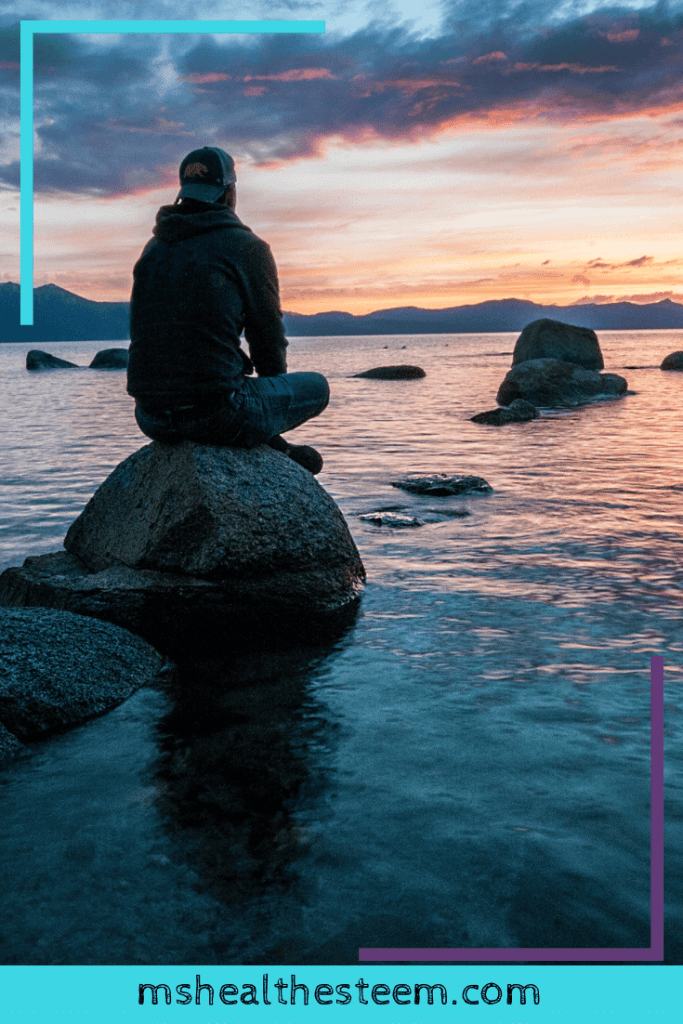 A man sits on a rock in the water, back to the camera, reflecting and meditating.