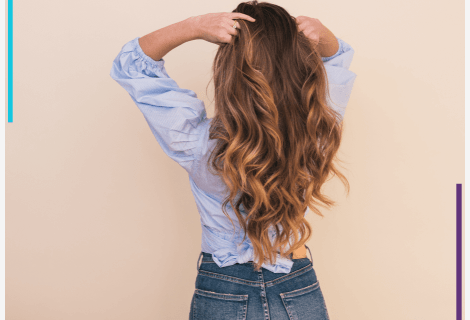 A woman stands back to the camera, running her fingers through her hair.