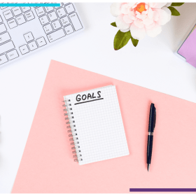 "An open notebook with the word ""Goals"" written at the top sits on a pink Bristol board. There's a pen sitting beside it. The Bristol board is on top of a white table, decorated with pink flowers. There's a keyboard on the top right and post its on the top left."