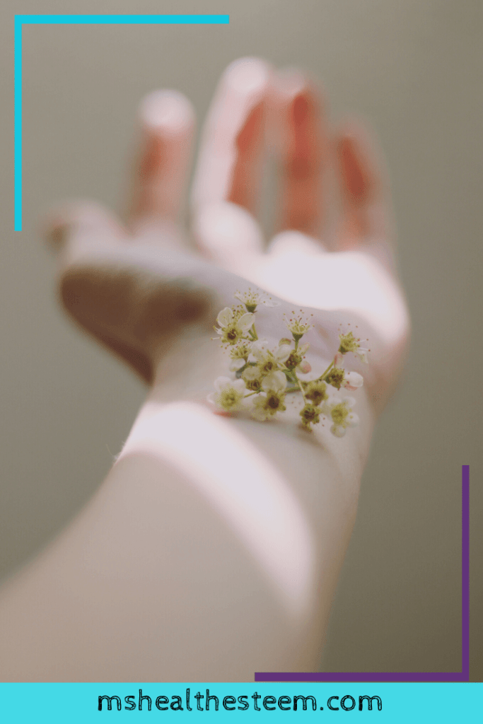 The camera focuses on flowers that sit delicately on someone's risk.