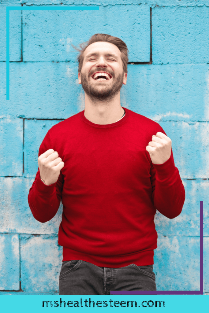 A man leans against a blue wall, fists up in joy, head tilted back, smiling and lauging as if enjoying a positive thought