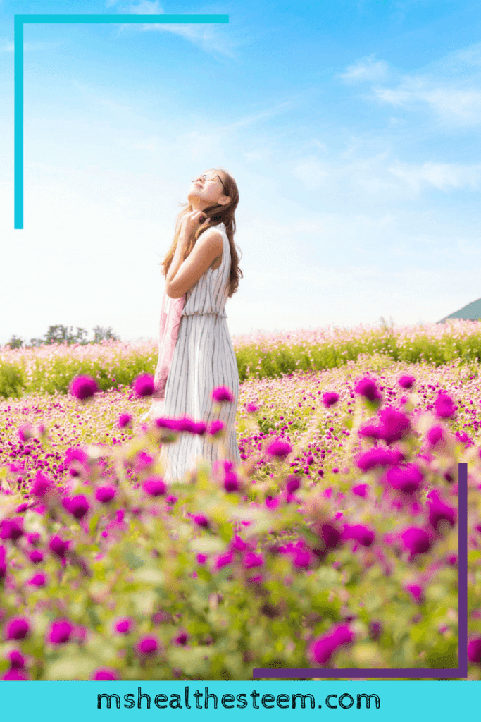 A woman stands in a field of purple flowersr. She looks up towards the big blue sky and closes eyes, as if enjoying the sunshine.