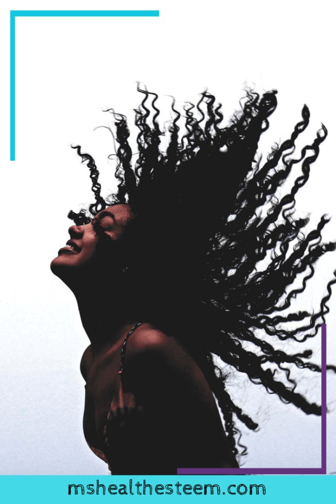 A woman smiles while flipping her hair back joyfully.