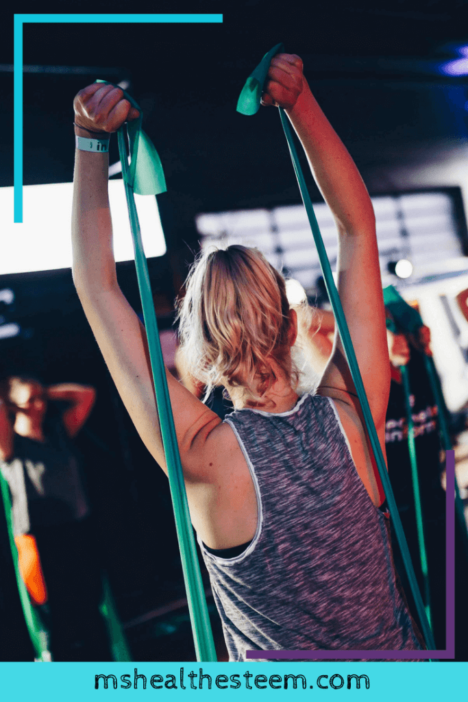 A woman works with a resistance band at a gym.