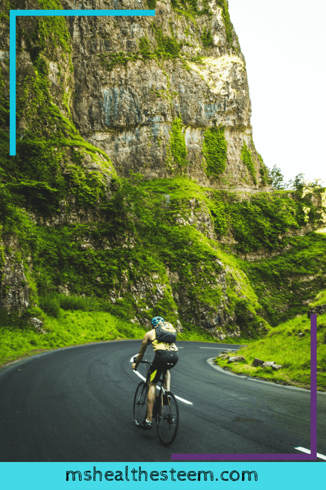 Man biking on scenic road, mountains and greenery can be seen in the background.