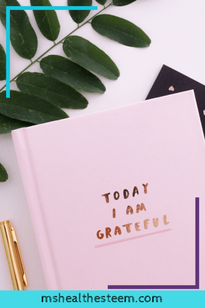 """A pink journal that says """"Today I am grateful"""" with a pen ready by it's side"""