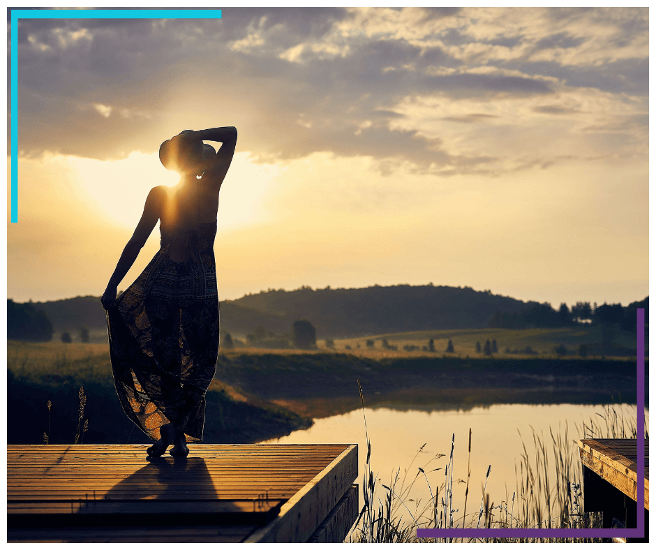 The silhouette of a woman standing on a dock, facing away from the camera and looking out at the water