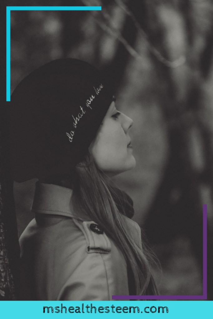 """A woman leans against a tree. She's wearing a touque with thepositive affirmations """"Do what you love"""""""