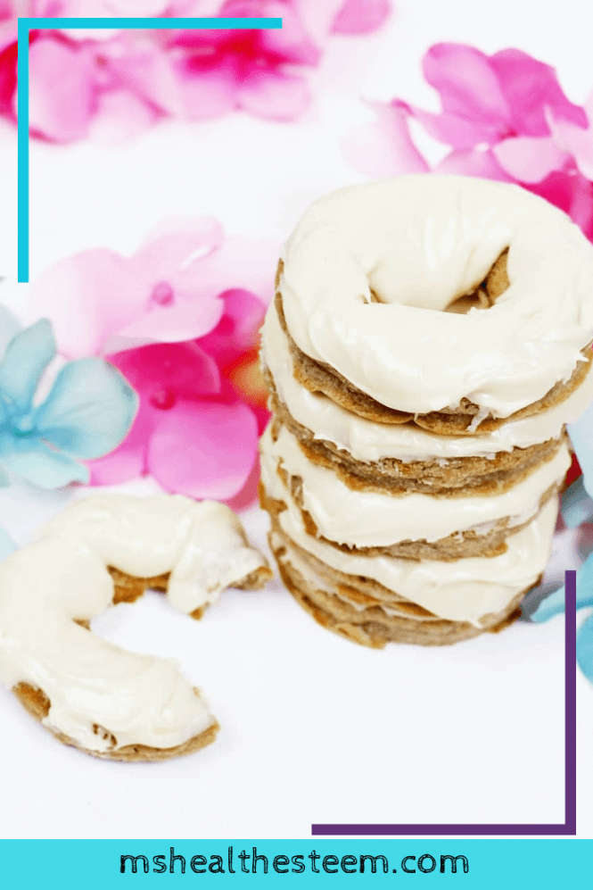 A stack of gluten free donuts frosted with maple butter and styled with pink and blue flowers. One has a bite taken out of it.