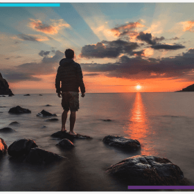 A man stands facing the water while the sun sets beautifully in the background.