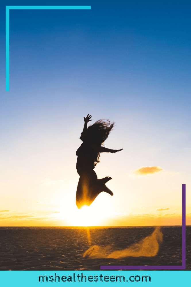 A woman jumps up in the air in joy. The sun is setting in the background and the sky is clear and deep blue.