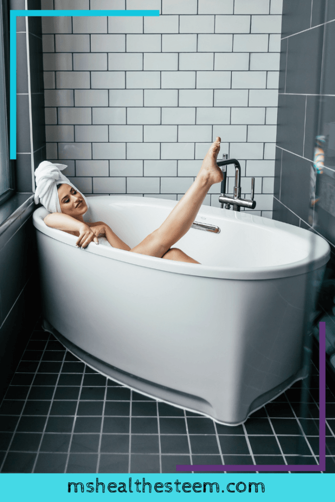 A woman lays in the tub, smile on her face and leg kicking in the air.