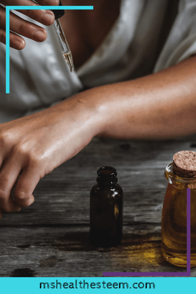 Someone tests a drop of essential oil on their wrist. It's so important to do a patch test before using a peppermint essential oil salve topically on your sensitive stomach.