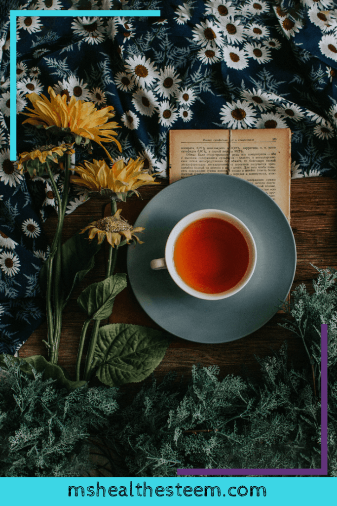 A cup of tea sits on a table with flowers, a book and a flowery table cloth. Tea can be a huge help to a sensitive stomach.