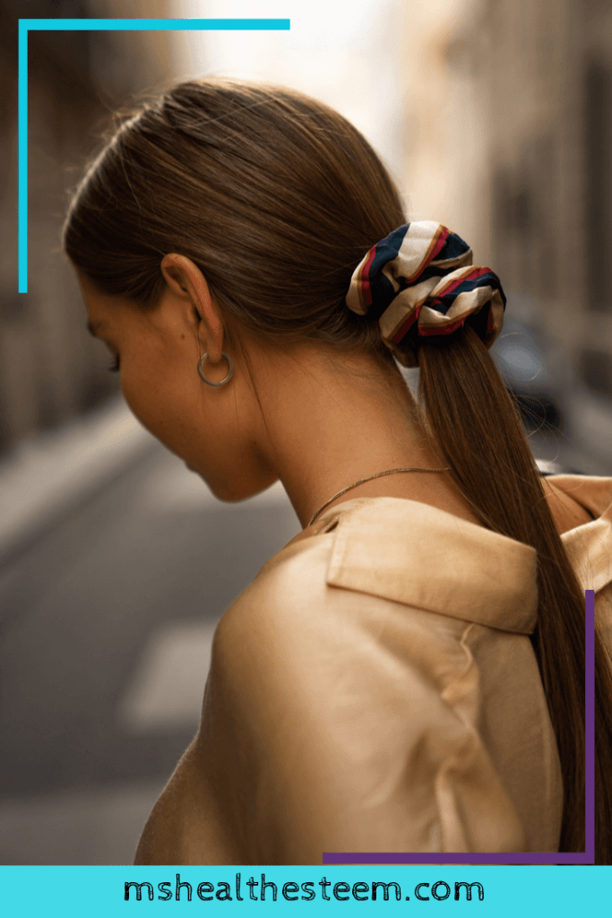 A woman looks away from the camera. Her long, shiny hair is in a ponytail, held up by a colourful scrunchie. Homemade deep conditioners can help to give your hair shine.