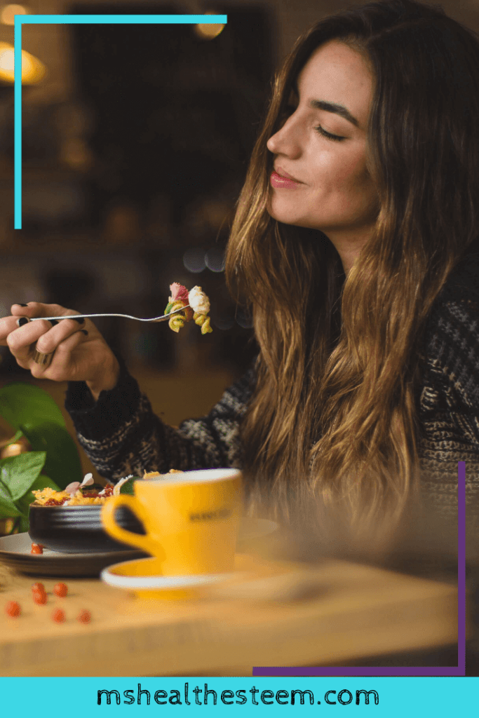 A woman sits at a table enjoying a meal by herself. Taking yourself out on a date can be a wonderful part of being self-partnered.