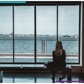A woman sits in front of a window, watching the ocean outside