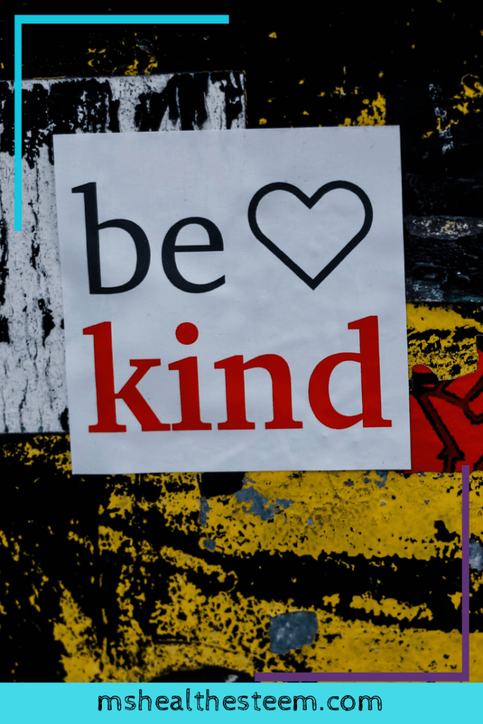 "A wall splattered with different colour paints with a sign that says ""Be Kind"" - A reminder to work to let go of any fatphobia and be kind to people."