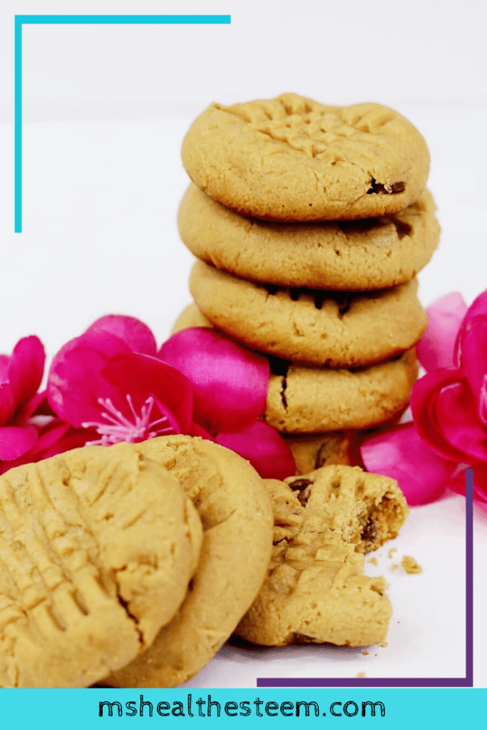 A pile of chocolate chip peanut butter cookies sit on a white table, decorated with pink flowers