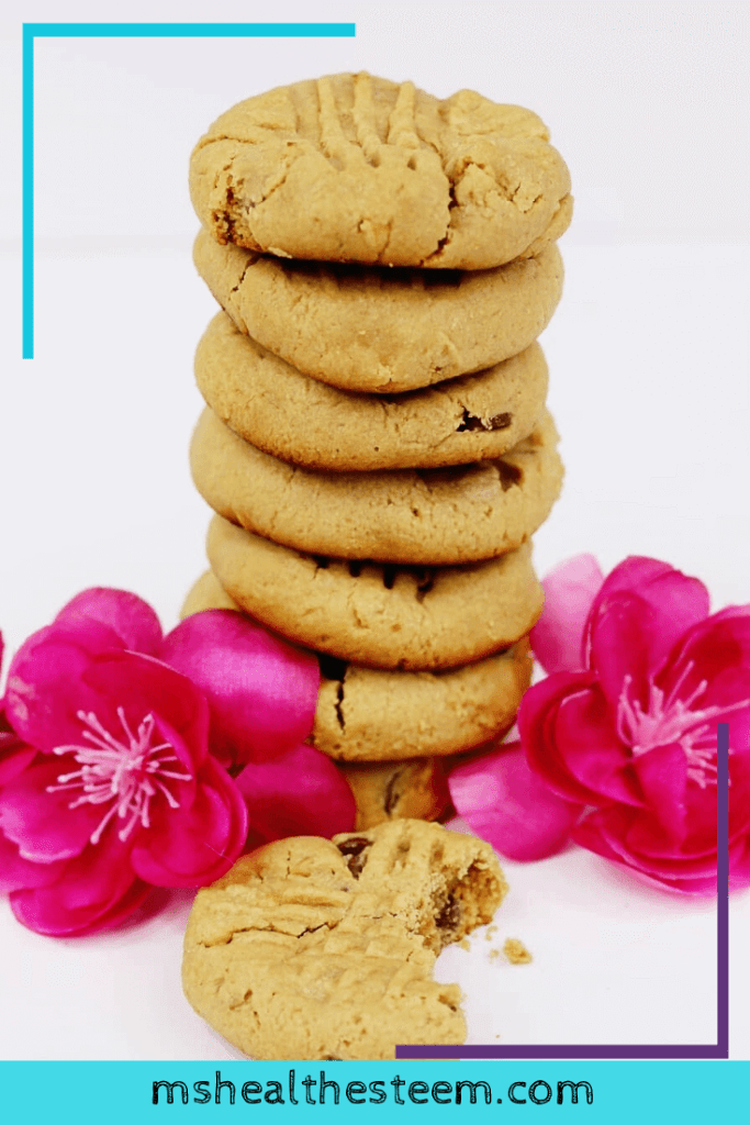 A pile of the best peanut buter cookies sit in a stack, decorated with pink flowers. One cookie with a bite out of it sits in front of the stack.
