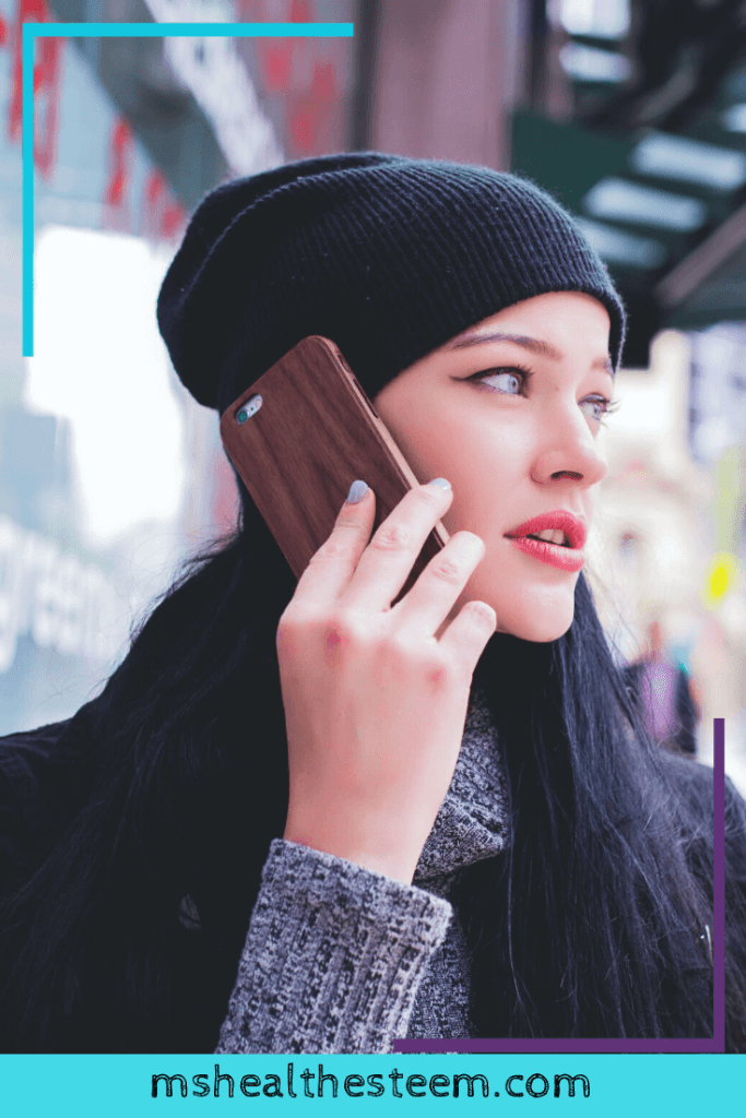 A woman holds a cell phone up to her ear and looks off to the side.