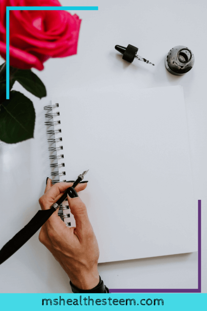 Someone's hand pauses abow a black page. They are holding a pen, as if ready to write. Writing yourself a love letter is a great way to lift your spirit.