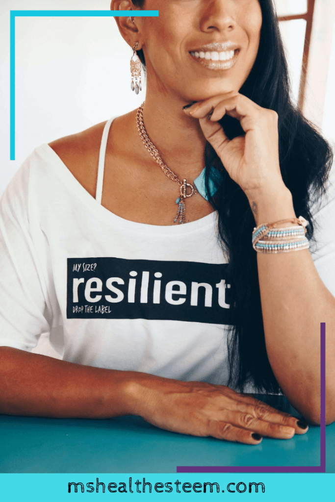 """A woman smiles and rests her chin on her hand. Her shirt says """"resilient."""" You too are resilient as you work to accept your body."""
