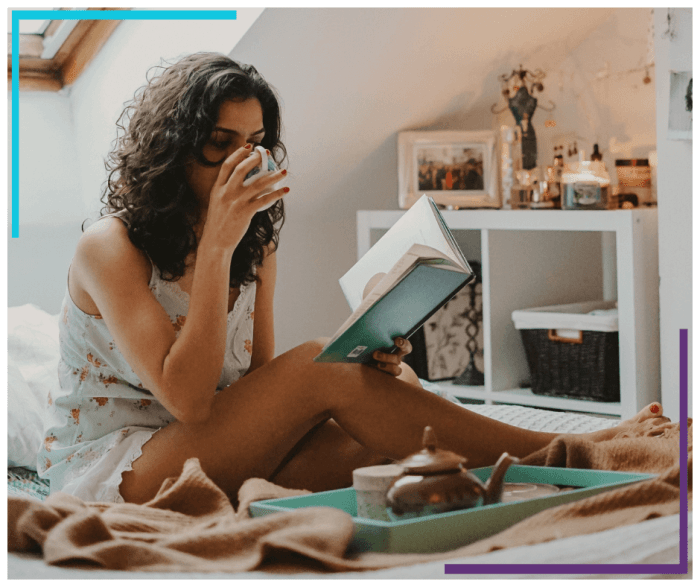A woman sits on her bed and sips tea while she reads a book