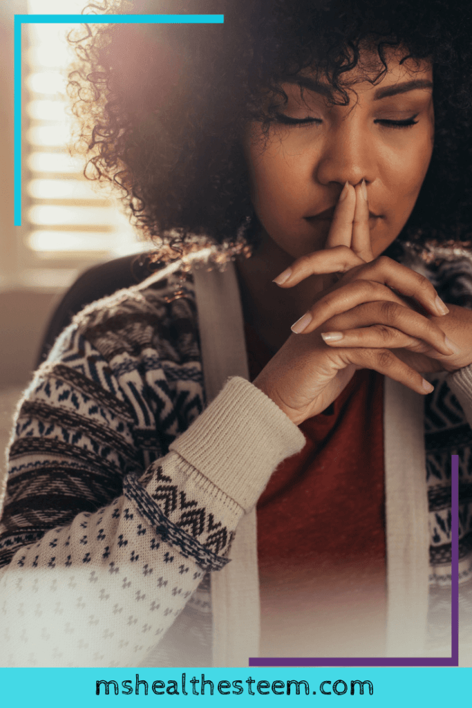 A woman sits with her eyes closed, with her hands clasped. Her two pointer fingers point up and she rests them on her lips. Her eyes are closed and she seems to be meditating. The importance of rest includes allowing you to experience mindful moments and connect with yourself.