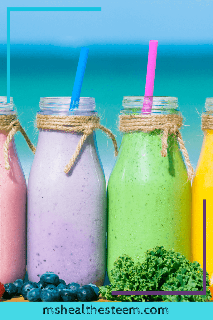 4 Smoothie glasses sit in a row. From left to right they are pink, purple, green and yellow. Each has a straw sticking out. And in front of the smoothies are fruits and vegetables, including strawberries, blueberries, kale and oranges.