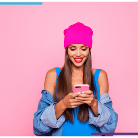 Photo of a woman wearing a jean jacket and pink tuque holding and looking at her cell phone. The background is also bright pink