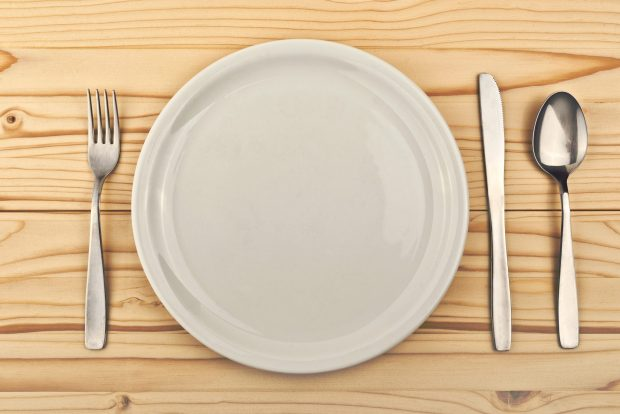 Empty plate on wooden table with tableware as concept for hunger and feeding, also a copy space for your text or design.