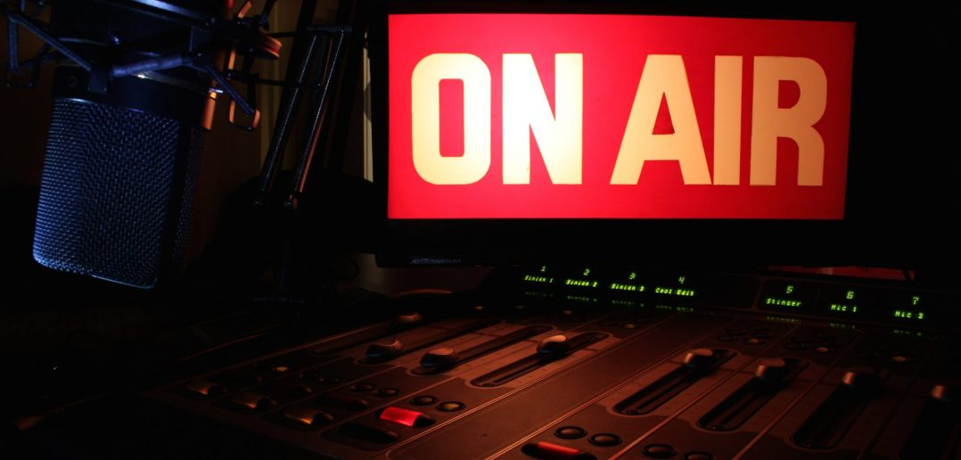 On Air sign glowing, reflecting light on a radio studio broadcast panel.