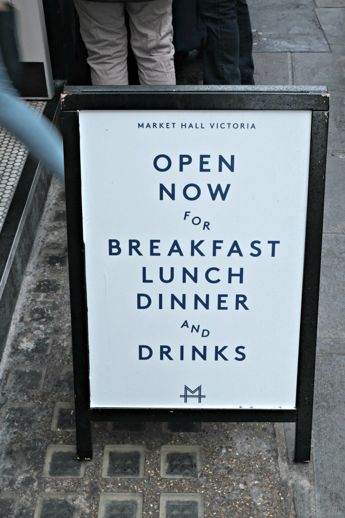 Picture of the sandwich board outside the Marks.et Hall Victoria saying now open for breakfast, lunch and dinner and drink