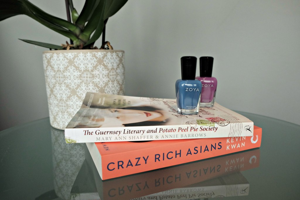 This image is a close up of two books on a side table with Zoya nail polish stacked on top of them.  There is a stack of books for my spring reading list.