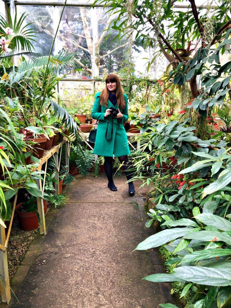 PIcture of me in the greenhoues holding my camera and smiling at hte camera.
