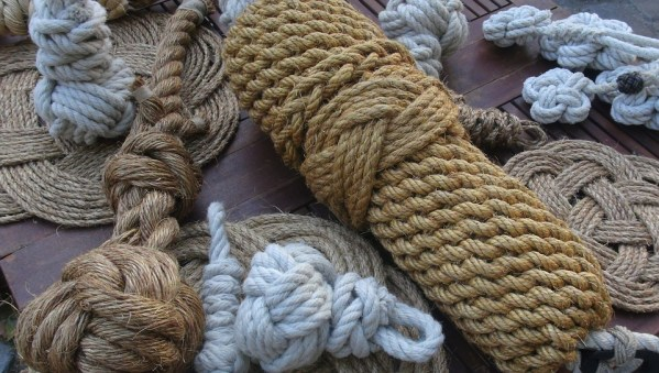 Image description: a variety of rope in decorative bundles. There is a large bundle of woven brown natural fiber rope, two smaller bundles of white cotton rope and other small pieces of brown rope in the background.