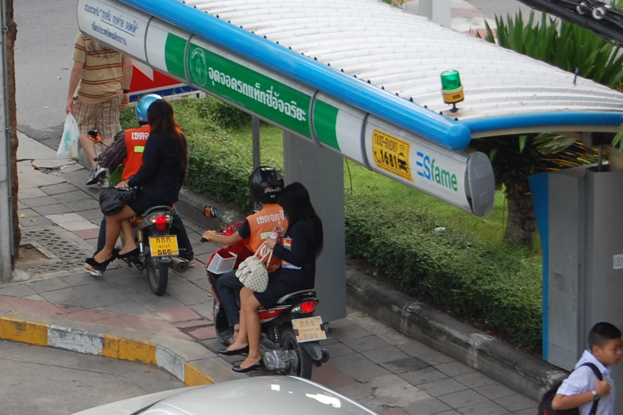 Motorbike taxis -- if I ever live in Thailand, I want to master the ladylike art of riding to work sidesaddle on the back of a motorbike that zips and zigzags through traffic, coming within centimeters of cars, busses, and ONCOMING traffic. And yes, as you see in this photo, it's perfectly legal in Thailand to ride a motorbike on the sidewalk.